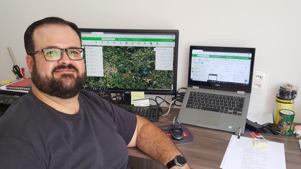 foto do consultor financeiro Alexandre Coser sentado em sua mesa de escritório com notebook e monitor abertos no Aegro