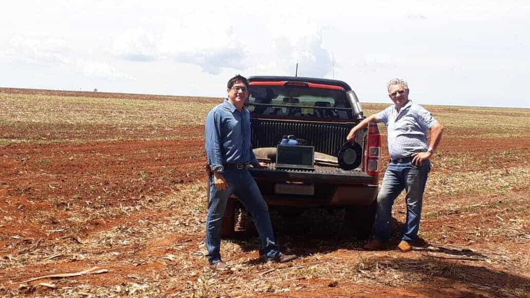 produtor e consultor no campo encostados na carroceria de uma caminhonete vermelha - Lucro histórico com gestão agrícola