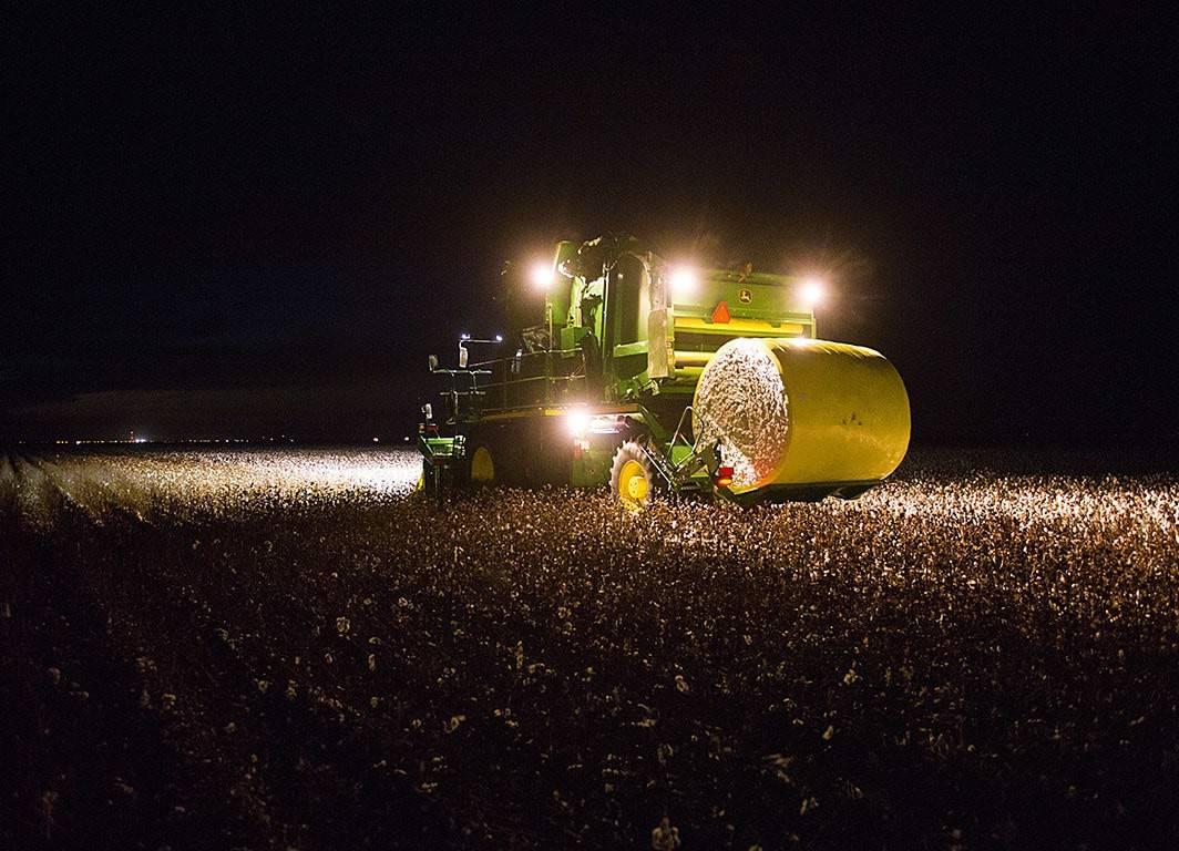 foto de colhedora de algodão de fusos operando durante a noite  - cálculo de semeadura do algodão