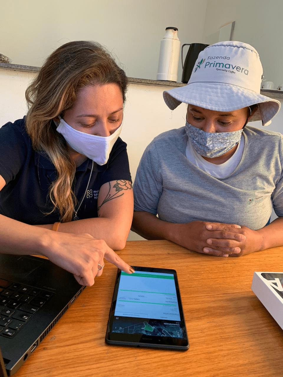 foto de duas mulheres usando máscara de pano, camisetas, sentadas em um escritório fazendo monitoramento de pragas de café e planejamento das operações com insumos pelo aplicativo Aegro. O tablet está numa mesa de madeira.