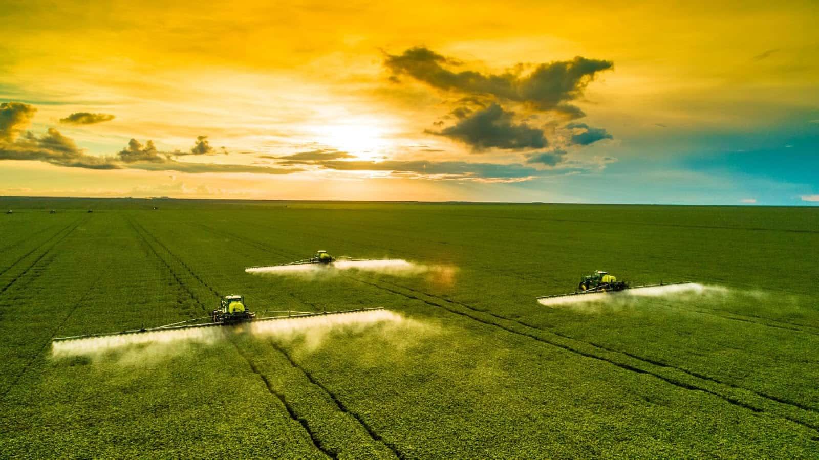 três máquinas agrícolas realizando pulverização em uma lavoura de soja com destaque para o horizonte e pôr do sol. Agricultura digital e planejamento safra