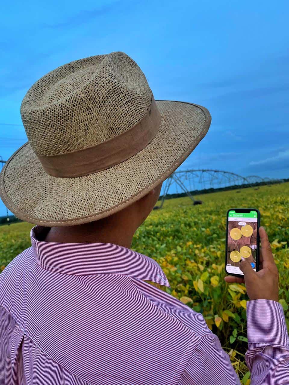 produtor rural Fernando Ishikawa virado de costas com um chapéu de palha, no meio da lavoura de soja, segurando um celular que mostra o monitoramento da área pelo sistema de gestão rural Aegro