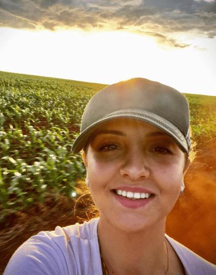 foto da Kamila Caneppele, sócia-proprietária da Fazenda Sagrada Família, na região de Caarapó, Mato Grosso do Sul. Ela está no meio da lavoura de milho, como se estivesse em movimento, com um boné, camiseta e sorrindo para a câmera.
