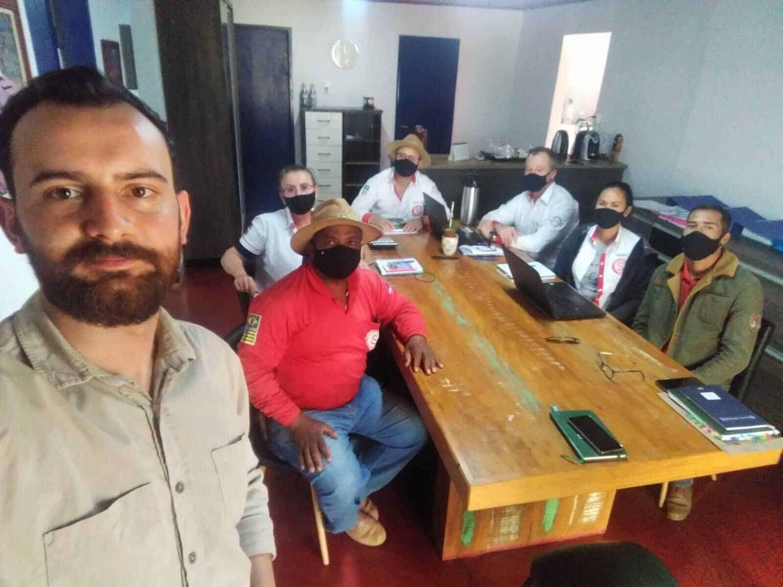 O consultor de controladoria e gestão financeira George Vital e a equipe da fazenda Schangri-lá. George está de pé e restante da equipe está sentado em volta de uma mesa de madeira.