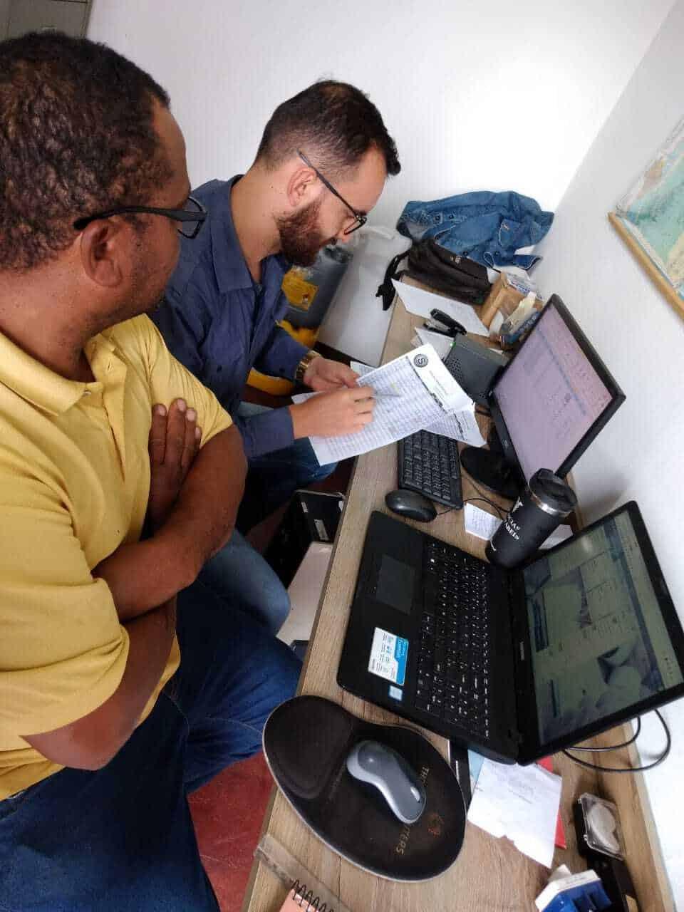 Imagem mostra consultor de controladoria e gestão financeira e funcionário sentados à mesa, em frente a dois computadores. Os dois olham para uma folha de papel.