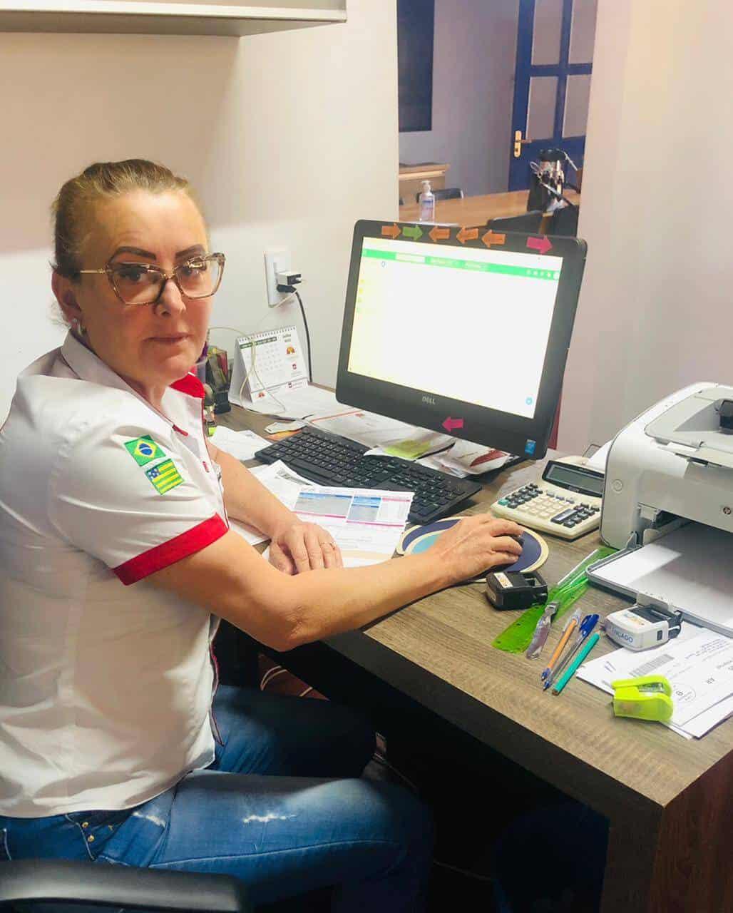 A imagem mostra outra funcionária da fazenda Shangri-lá, também em frente ao computador. Ela usa óculos e está com os cabelos presos.