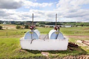 Tanque de armazenamento de combustível em uma fazenda. Há dois galões de diesel em um suporte de concreto, com um grande campo no fundo.
