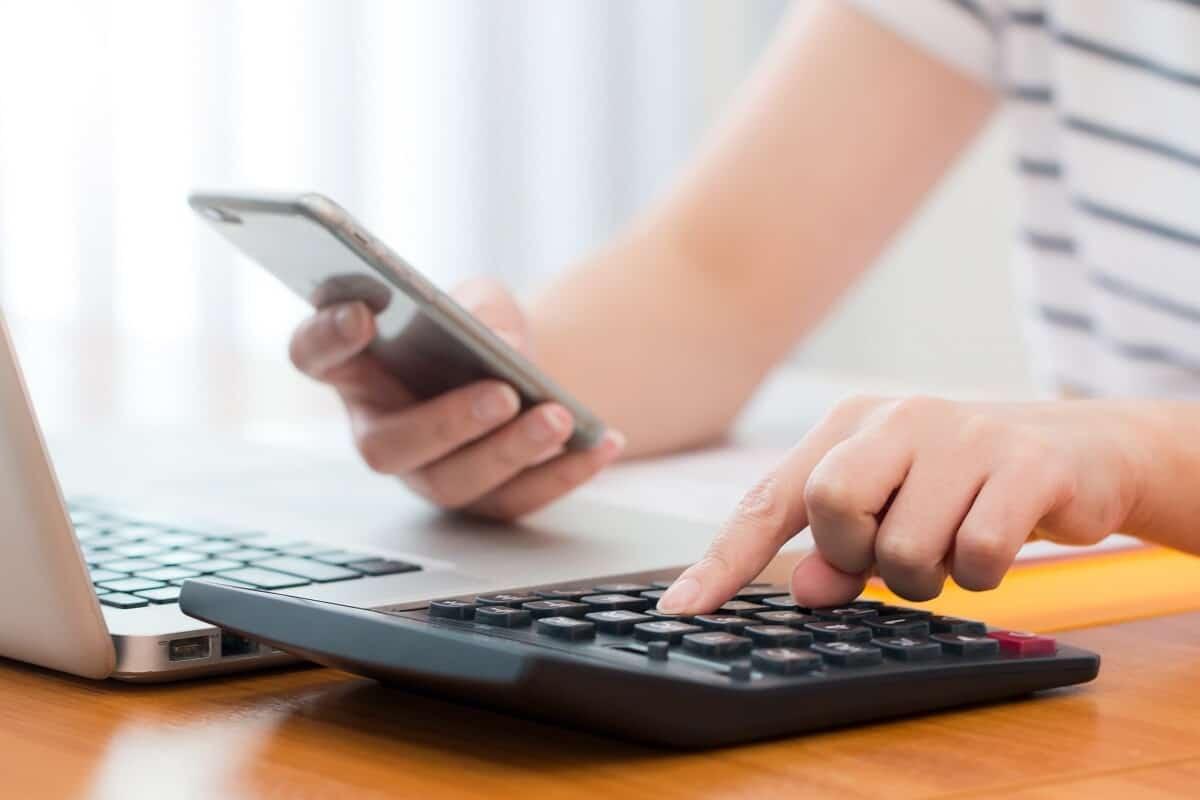 elaboração de projetos de crédito rural: imagem dos braços de uma mulher que mexe no celular e faz cálculos usando uma calculadora. Na frente dela, há um laptop.