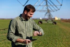 Imagem mostra homem jovem em uma fazenda, sorrindo e olhando para um relógio no pulso.