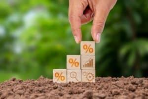 Imagem mostra uma mão segurando um quadrado com símbolo da porcentagem, que está em cima de outros quadrados sob um solo de plantio. No fundo, há uma paisagem verde desfocada.