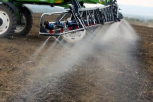 Imagem de máquina agrícola despejando defensivo em solo